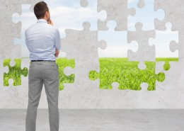 business, people, ecology and strategy concept - businessman thinking from back over puzzle with natural landscape and concrete room background